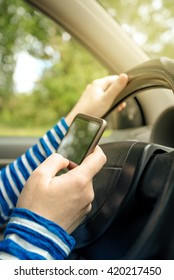 Woman driving car and reading received message on smartphone, using mobile in traffic.