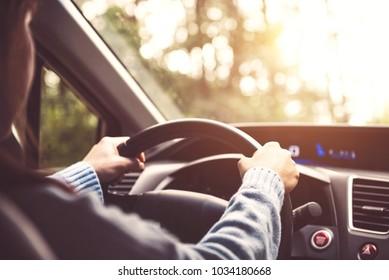 Woman driving car at sunset.
