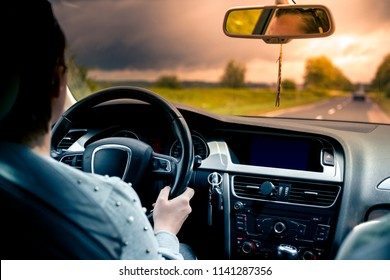 A woman is driving a car at sunset.