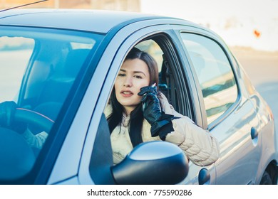 woman driving car and talking on mobile phone.