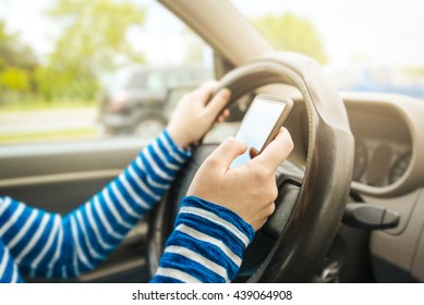 Woman driving car and texting message on smartphone
