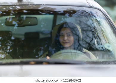 Woman driving a car viewed from the front through the windscreen with reflections of trees on the glass