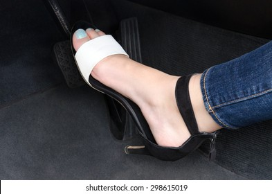 Woman driving the car; women's leg on heels pressing the brake pedal in the car; Inconvenient footwear for driving