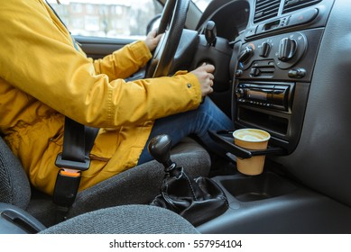 woman driving with coffie in cup holder