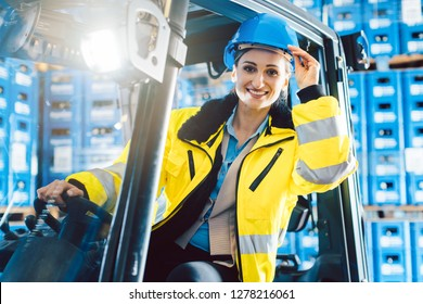 Woman driving a forklift in logistics delivery center looking into the camera