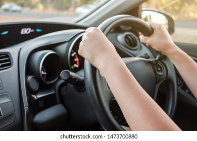 Woman driving her car with both hands on steering wheel