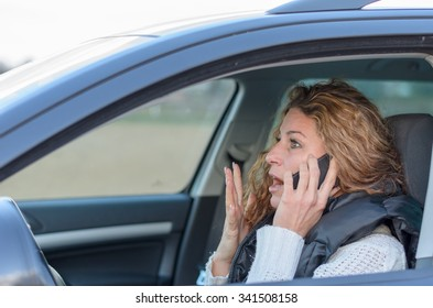 woman is driving her car with a shocked expression while having a call