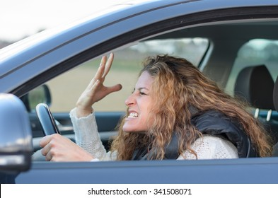 woman is driving her car very aggressive and gives gesture with his fist