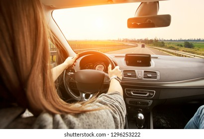 The woman driving the modern car on the asphalt road toward the sunset