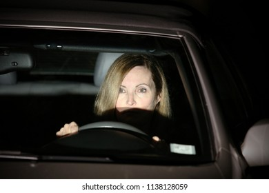 A woman is driving at night; the headlights from the oncoming car are lighting her face.