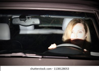 A woman is driving at night; the oncoming car has its high beam headlights on.