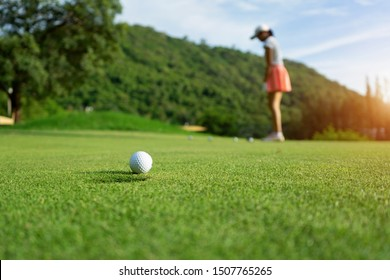 Woman driving practice golf or trainer at golf course on the fairway at sunset