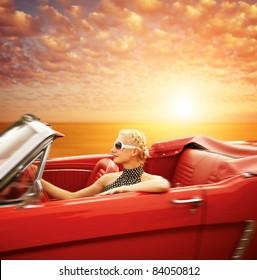 Woman driving retro car against beautiful sky.