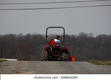 Woman driving a tractor on a farm shot from behind