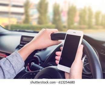 Woman driving and using smartphone on the road, Concept of smartphone addiction, phubbing or social network issues
