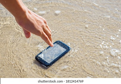 The woman dropped her smartphone into the sea. Lost mobile phone on a sandy beach.