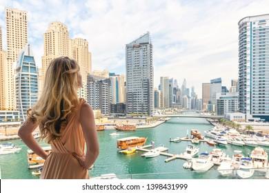 Woman in Dubai Marina, United Arab Emirates. Attractive lady wearing a long dress admiring Marina harbor daylight view