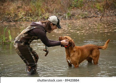 Woman Duck Hunter petting Labrador Retriever in Pond