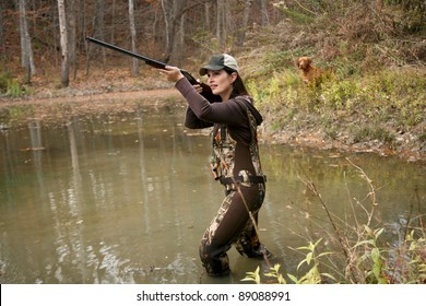 Woman Duck Hunter wearing Camo Waders with Rifle in Pond and Dog in Background