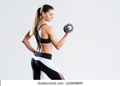 Woman with dumbbell fit slim abs body isolated on a white background. Healthy lifestyle.