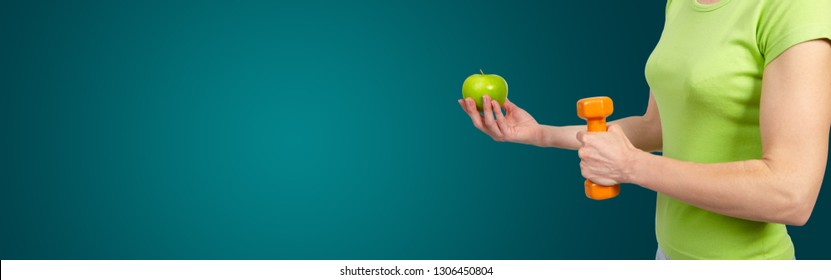 Woman with a dumbbells and apple. On green background