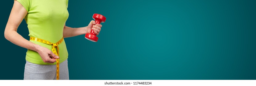 Woman with dumbbells. On green background. Sport