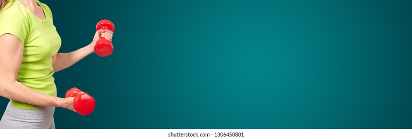 Woman with a dumbbells. On green background