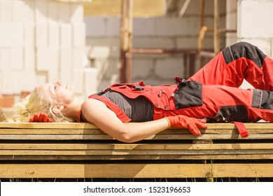 Woman in dungarees relaxing after hard work on construction site. Young female lying outdoor taking a break