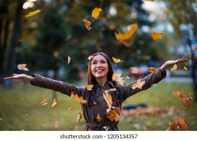 Woman during autumn, lifestyle concept. An Asian young adult female is enjoying the sunny weather during Fall, in a park with fallen yellow leaves. Communicate about season, enjoying nature.