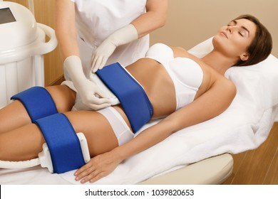 Woman during Cryolipolysis procedure in professional beauty clinic