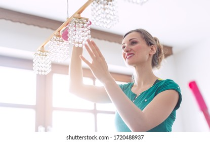 Woman dusting a lamp during spring cleaning in her apartment