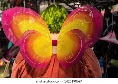 Woman with dyed green hair wearing and red, orange and yellow butterfly wings at a renaissance fair.