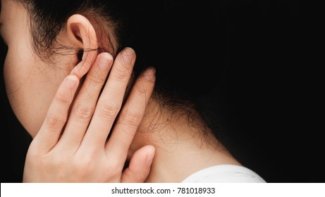 woman with ear pain or neck pain.Acute pain in a woman Throat . Female holding hand to spot of Behind the ear. Concept photo with read spot indicating location of the pain.