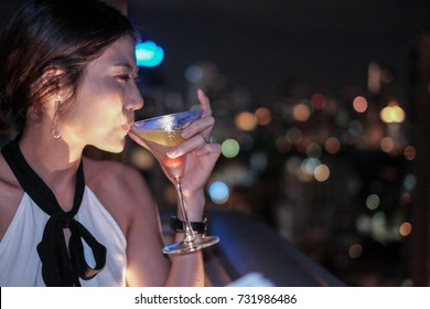 Woman with ear rings at party deck drinking glass of cocktail at night time with beautiful bokeh background, asian girl party portrait