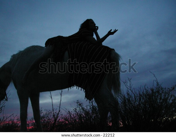 A woman in the early evening gestures from the top of her horse.