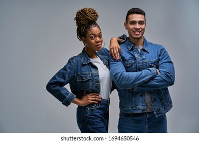 Woman in earrings with bun of braids with man with smiles stand and look at camera