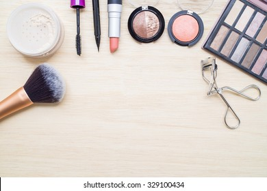 Woman earth tone cosmetics - eyeshadow, brush on, lipstick, eye liner, mascara, powder, brush, eyelash curler. Top view with space for text.