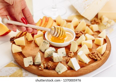 Woman Eat Big Italian Cheese Board Gourmet Food with Honey Side View. Girl Taste French Cheeseboard with Brie, Parmesan and Mozzarella Assorted. Blue Cheddar, Gouda and Walnut Various Dessert Platter