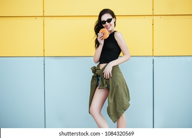 Woman eat Fast food. Portrait of beautiful girl in fashion casual clothes and trendy sunglasses laughing and eat burger outdoor on yellow urban background. Fast food Street style Lifestyle concepts