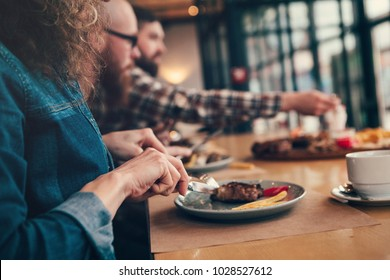 Woman eat meat in cafe with friends.