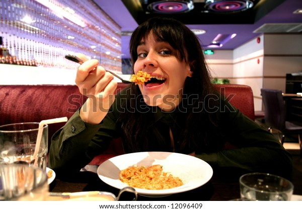 a woman eat rice in a restaurant