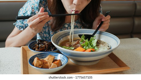 Woman eat Taiwanese braised beef noodles at restaurant