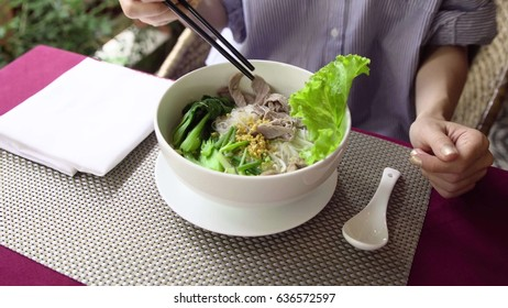 Woman eat traditional Vietnam Pho Bo beef noodle soup with chopsticks.