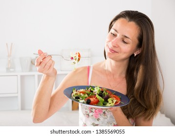 Woman eating an appetizing salad in bed