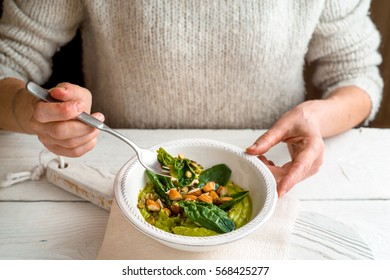 Woman eating avocado cream with almond and spinach  horizontal