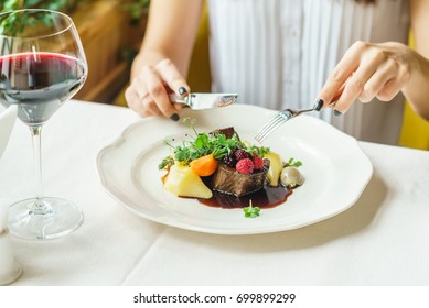 woman eating beef steak with berry sauce