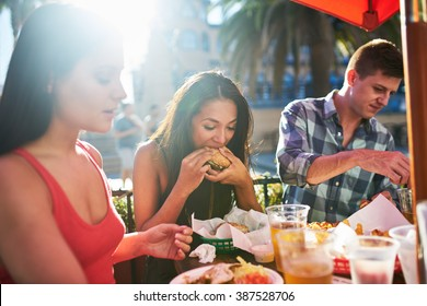 woman eating big burger together with friends at outdoor restaurant
