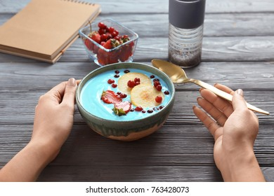Woman eating blue spirulina smoothie at table. Healthy vegan food concept