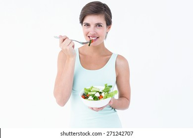 Woman eating bowl of salad on white background