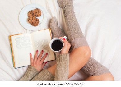 Woman eating breakfast in bed while reading a book .
